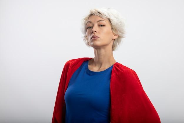 Superdonna sicura con mantello rosso che guarda davanti isolato sul muro bianco