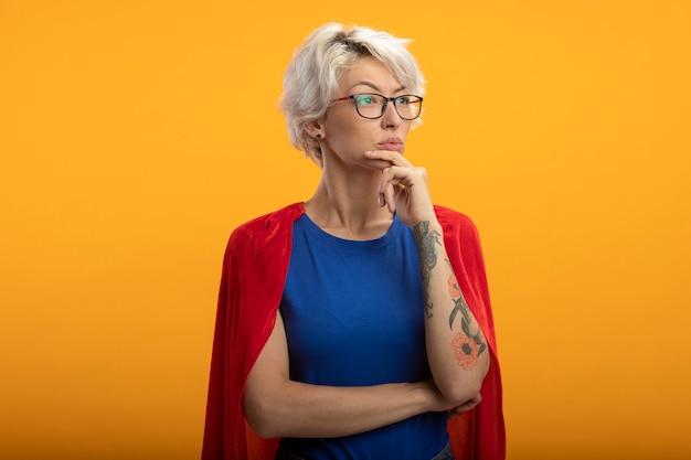 Fiduciosa superdonna con mantello rosso in vetri ottici mette la mano sul mento e guarda a lato isolato sulla parete arancione