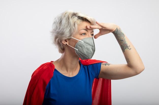医療マスクを身に着けている赤いマントを持つ自信のあるスーパーウーマンは、白い壁で隔離された側を見て額に手のひらを保ちます