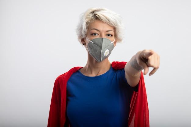 Superdonna sicura con mantello rosso che indossa punti mascherina medica nella parte anteriore isolata sul muro bianco