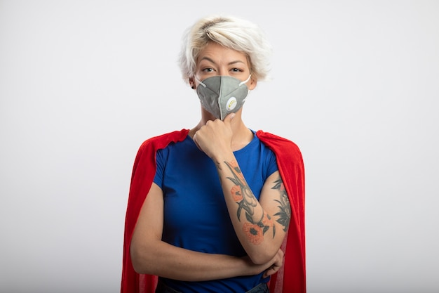 La superdonna sicura con il mantello rosso che indossa la mascherina medica mette la mano sul mento isolata sulla parete bianca
