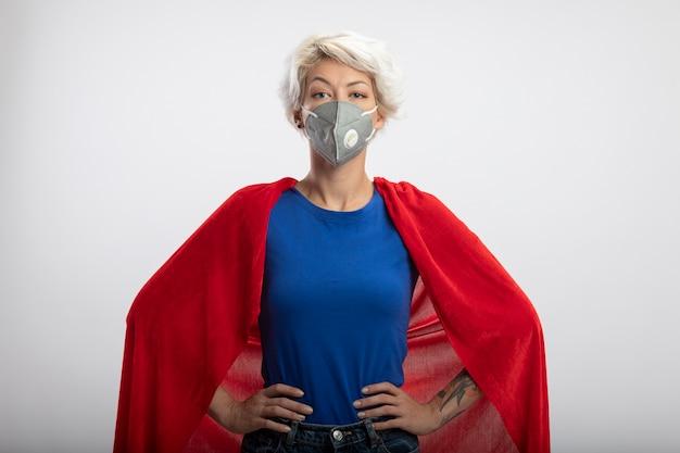 La superdonna sicura con il mantello rosso che indossa la mascherina medica mette le mani sulla vita isolata sulla parete bianca