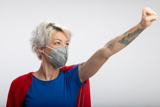 La superdonna sicura con il mantello rosso che indossa la mascherina medica sta con il pugno alzato e guarda al lato isolato sul muro bianco