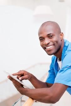 自信のある外科医。デジタルタブレットで作業し、手すりに寄りかかって笑っている青い制服を着た思慮深い若いアフリカの医師の側面図