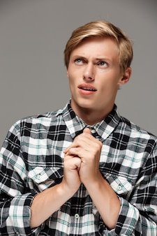 Confident surprised blond handsome young man wearing casual plaid shirt with hands ready to pray looking up  grey wall