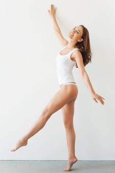 彼女の完璧な体に自信を持っています。白いタンクトップと白い背景に立ってポーズをとってパンティーの魅力的な若い女性の完全な長さ