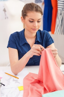 Confident tailor sewing. beautiful young woman sewing while sitting at her working place