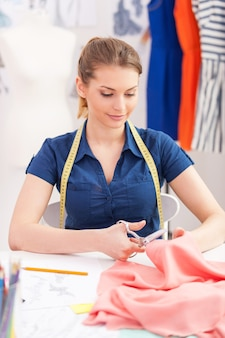 Confident tailor at work. beautiful young woman with measuring tape on shoulders cutting the cloth with scissors while sitting at her working place