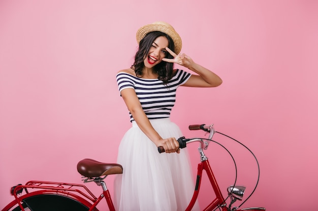 Confident tanned woman posing with bicycle and expressing happiness. indoor photo of debonair girl in romantic outfit  having fun.
