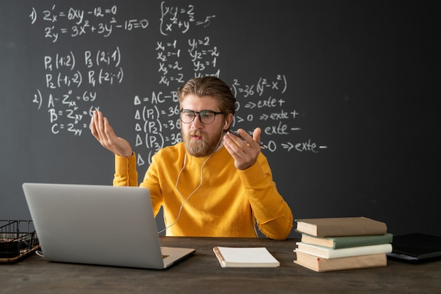 Confident teacher in eyeglasses looking at his audience on laptop display while explaining new formula on blackboard during online lesson