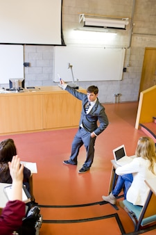 Confident teacher giving a lesson to university students