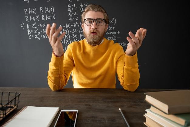 カメラの前で本とメモ帳を持ってテーブルのそばに座っている間、彼のオンライン学生に新しい主題を説明する代数の自信のある教師