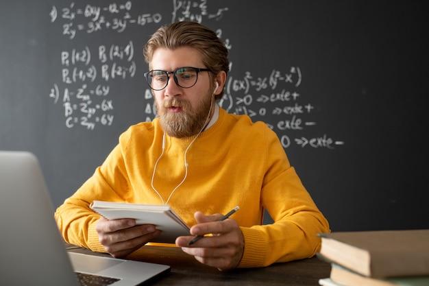 책과 메모장이있는 테이블에 앉아 온라인 학생들에게 새로운 주제를 설명하는 대수학의 자신감있는 교사