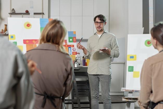 Уверенный учитель живописи объясняет своим ученикам основные правила профессионального рисования на уроке в художественной школе.
