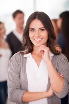 Уверенный в себе лидер команды. красивая молодая женщина, взявшись за подбородок и улыбаясь, пока группа людей стояла на заднем плане