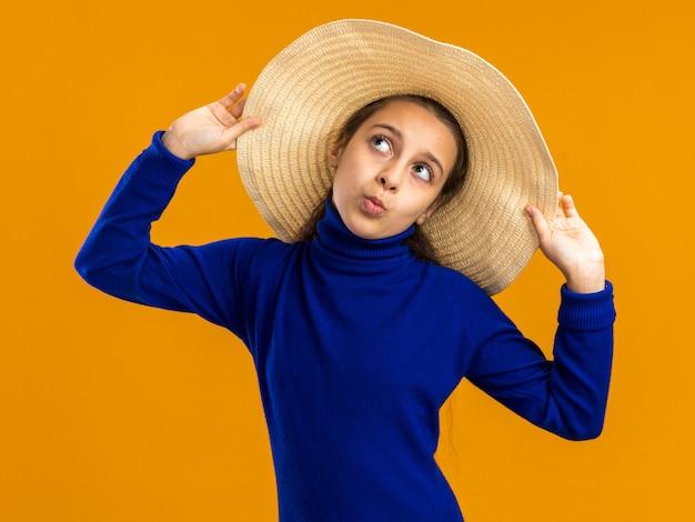 Adolescente fiducioso che indossa un cappello da spiaggia che lo afferra guardando in alto con le labbra increspate isolate sul muro arancione