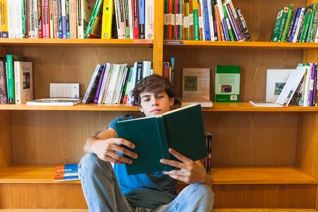Confident teenager reading on floor near bookcase
