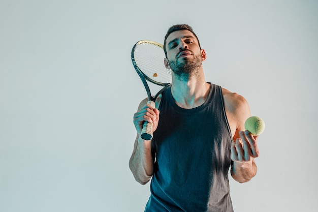 Confident tennis player hold ball and racquet. front view of young bearded european sportsman. isolated on gray background with turquoise light. studio shoot. copy space