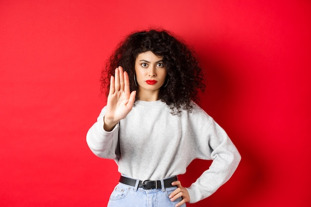 Confident tensed woman extend hand to say stop, disapprove action and prohibit it, make no gesture, standing on red wall and forbid something