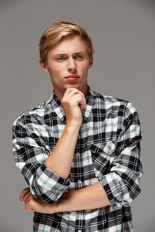 Confident thinking blond handsome young man wearing casual plaid shirt with hands crossed on chest looking away  grey wall
