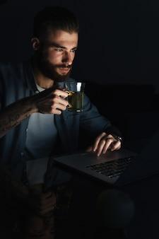 夜に屋内のテーブルに座って、お茶を飲みながらラップトップコンピューターで作業している自信を持って考える若い男