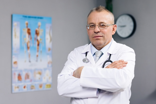 Confident thoughtful senior adult male professional medic old doctor wears white medical coat glasses holding stethoscope