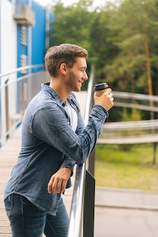 Confident thoughtful young man standing on balcony terrace and drinking coffee leaning on railing