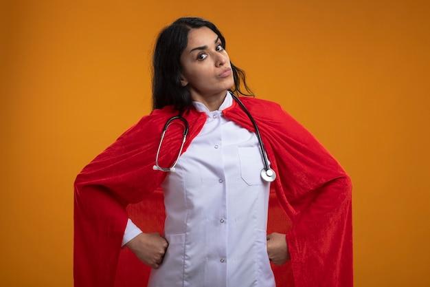 Уверенно наклонив голову молодая девушка супергероя в медицинском халате со стетоскопом, положив руку на бедро, изолированную на оранжевой стене