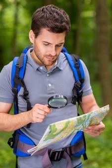 Уверенно туристическая изучающая карта. уверенный молодой человек с рюкзаком изучает карту с увеличительным стеклом, стоя на природе