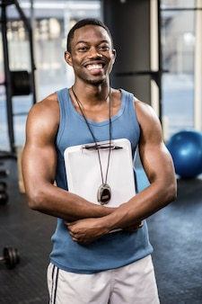 Confident trainer standing with clipboard at the crossfit gym