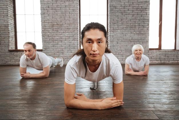 正面をまっすぐ見ながら床に腕を置く白いtシャツを着ている自信のあるトレーナー