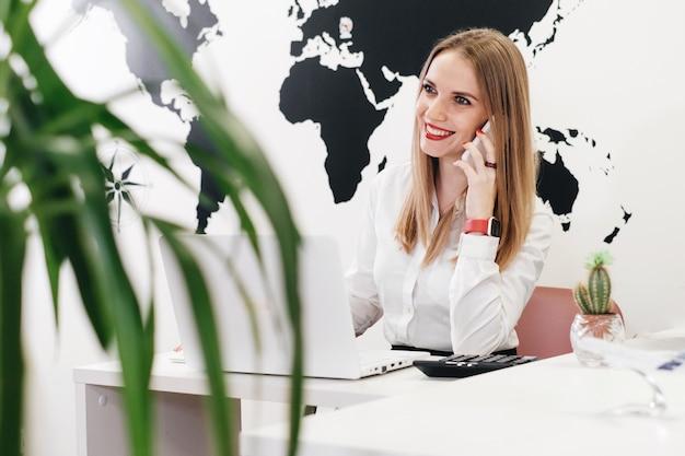 オンライン通信のために地図上でオフィスでラップトップを使用している自信のある旅行代理店 Premium写真