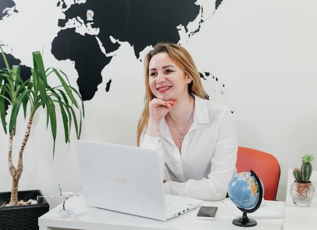 オンライン通信のために地図上でオフィスでラップトップを使用している自信のある旅行代理店
