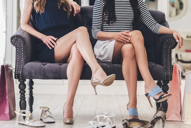 彼らの選択に自信を持っています。靴屋のソファに座っている間、膝で足を組んでいる完璧な足を持つ若い女性の一部