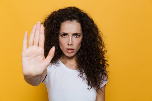 Confident woman 20s with curly hair doing stop gesture with hand isolated on yellow