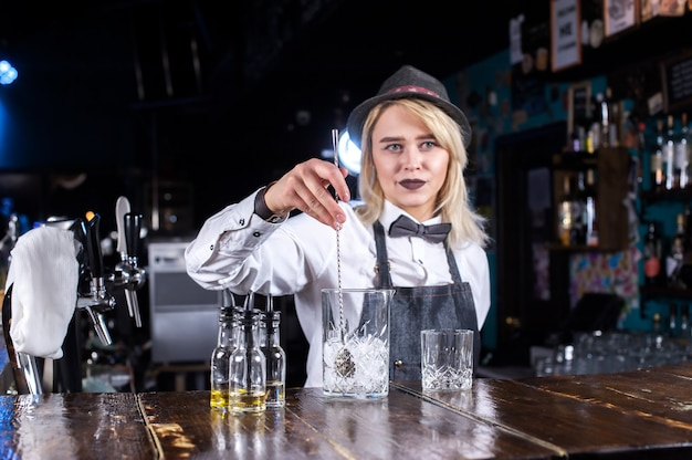 Confident woman barman demonstrates the process of making a cocktail