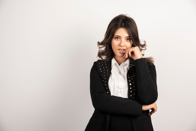 Donna sicura in giacca nera in piedi su bianco