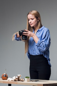 Confident woman in blue shirt taking food pictures