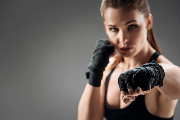 Confident woman boxing on a grey