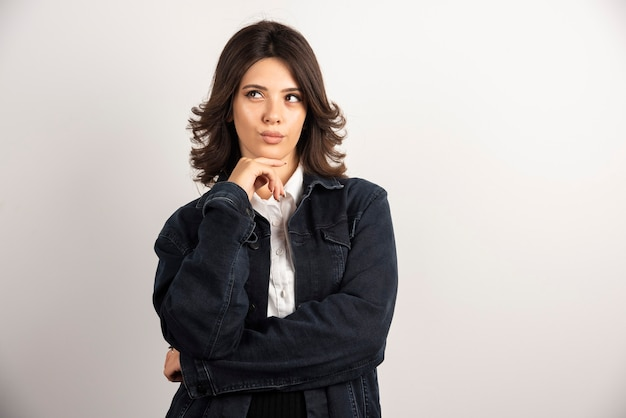 Donna sicura in giacca di jeans in piedi su bianco.