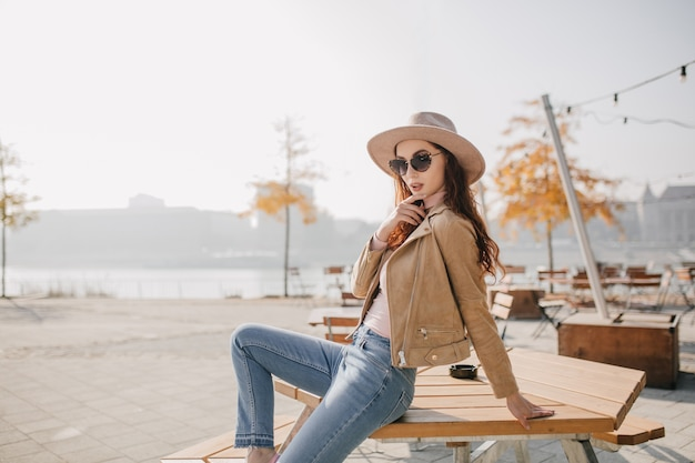 Confident woman in denim pants sitting on table in street cafe