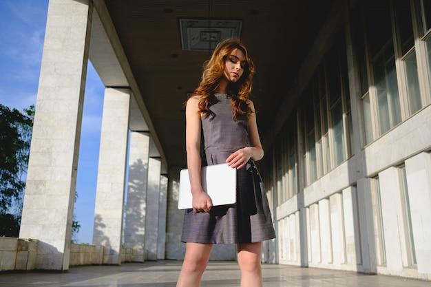 Confident woman holding a laptop