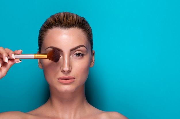 Confident woman holding a make up brush