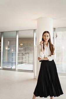 Уверенная в себе женщина в длинной черной юбке и белой блузке, скрестив руки на груди в самоуверенной позе.
