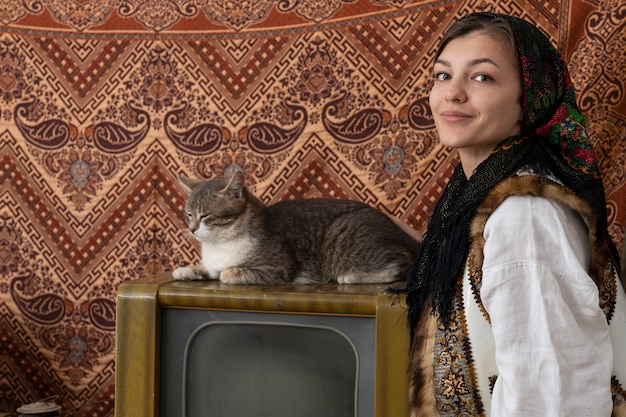 Confident woman in national clothes looking at the camera, grey cat sitting on the old tv