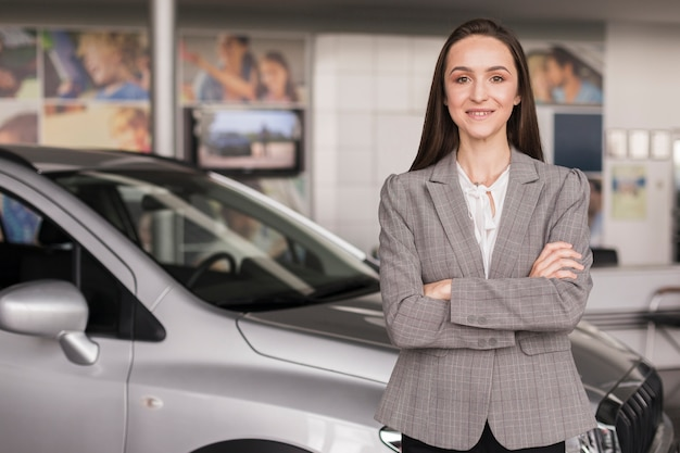 Confident woman posing in front of a car