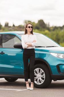 Уверенно женщина позирует перед автомобилем