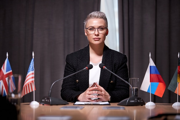 Confident woman sits with microphone holding business meeting, in formal wear, sits at desk in boardroom discussing business ideas and strategies