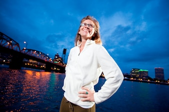 Confident woman standing at waterfront with urban bridge and cityscape in background