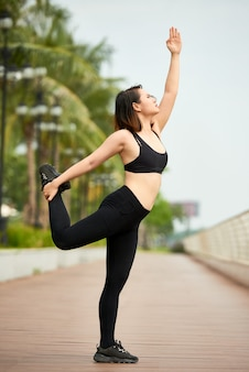 Confident woman stretching on street